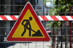 Road safety worker sign and barrier tape used to mark work site